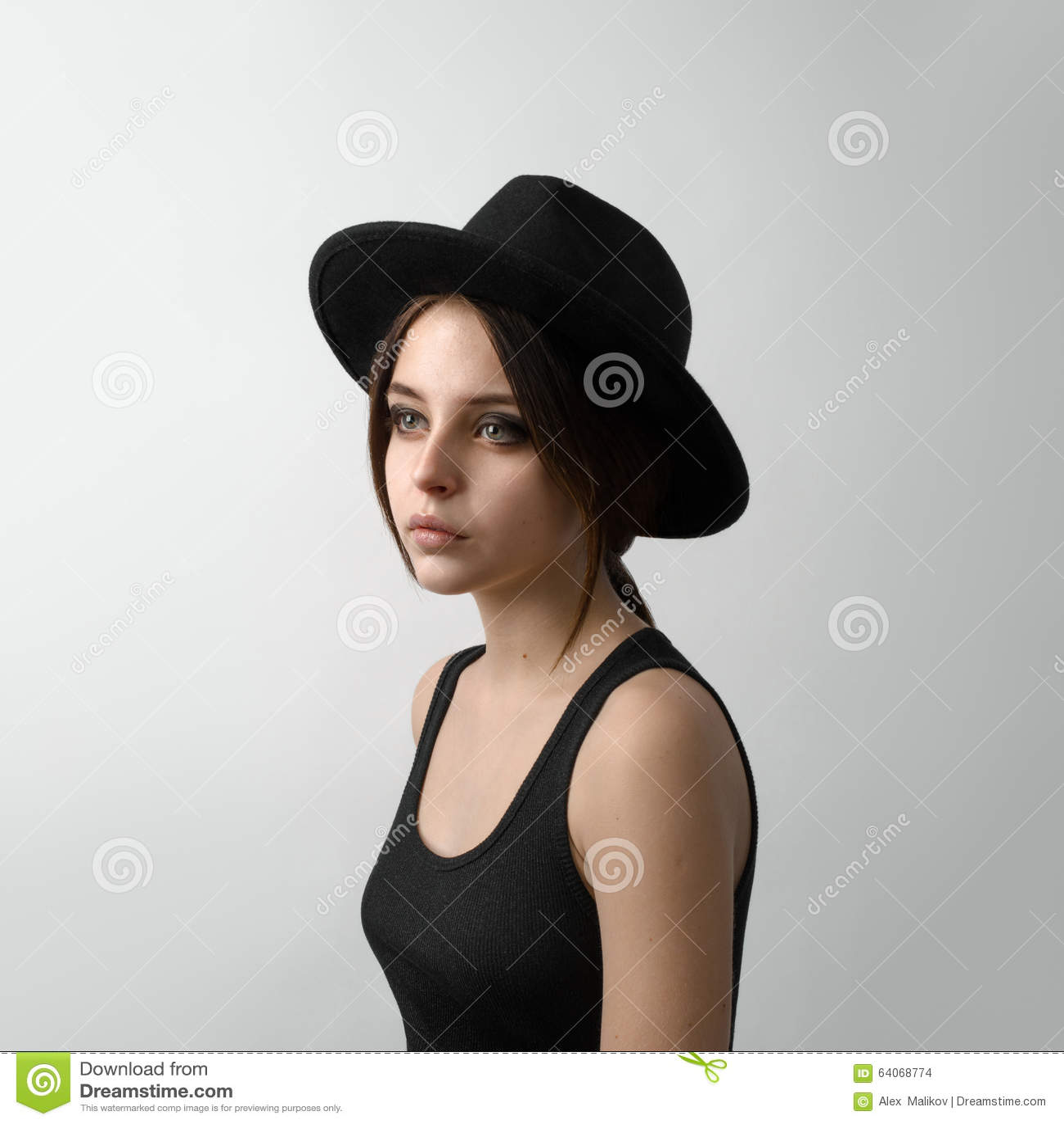 Dramatyczny portret dziewczyna temat: portret piękna młoda dziewczyna w czarnym kapeluszu i czarnej koszula na szarym tle