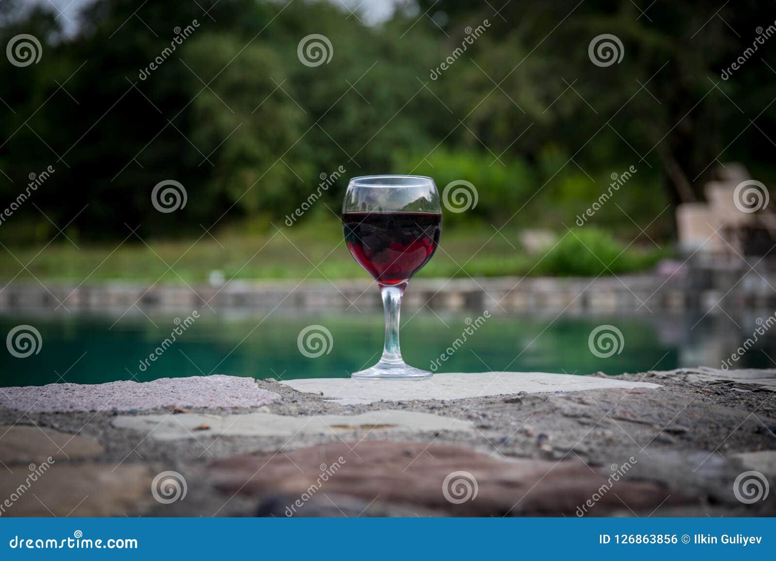 Drank in lang glas in poolside Verfrissing op de zomerdag Purpere sapcocktail of wijnstok Berg bosachtergrond