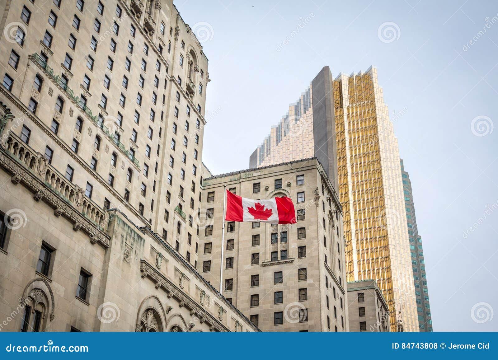 Drapeau canadien devant un bâtiment d affaires et un gratte-ciel plus ancien à Toronto, Ontario, Canada