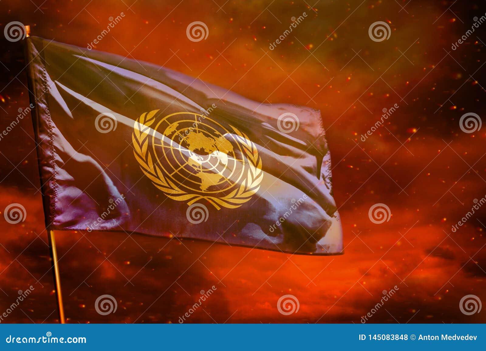 Drapeau de flottement des Nations Unies sur le ciel rouge cramoisi avec le fond de piliers de fumée Pr