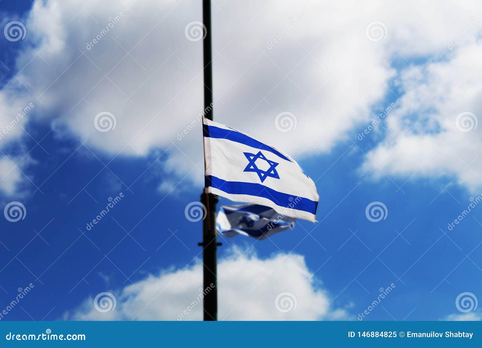 Drapeau de l Israël accroché en l honneur du Jour de la Déclaration d Indépendance de l Israël contre le ciel bleu