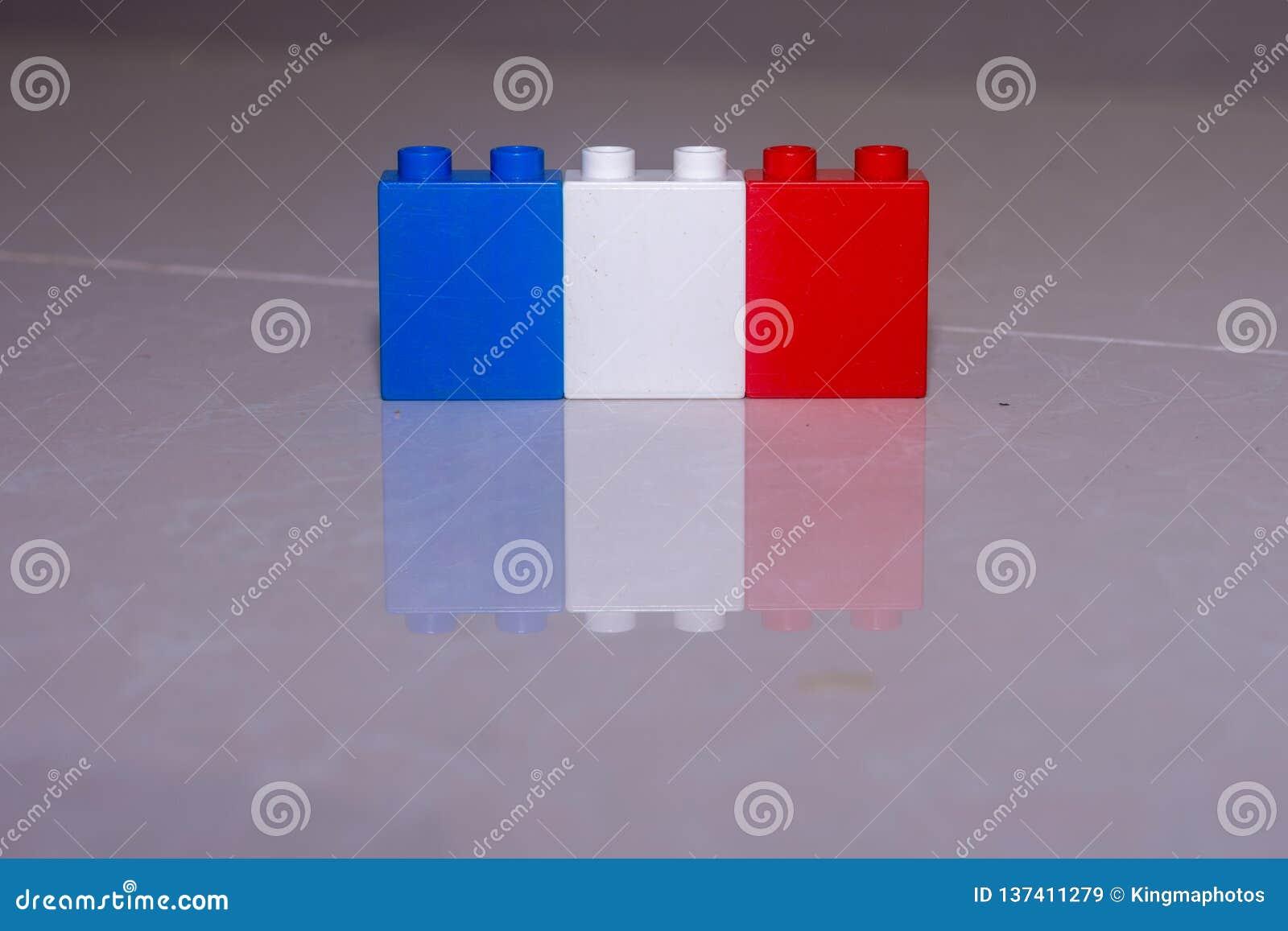 Drapeau français blanc, rouge et bleu fait de blocs de jouet sur une tuile avec une réflexion et un espace pour ajouter le concep
