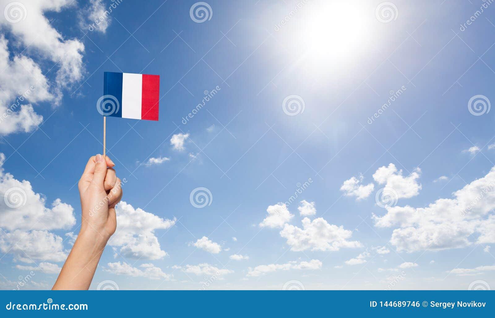 Drapeau français de participation de la main de la femme au-dessus du mât de drapeau