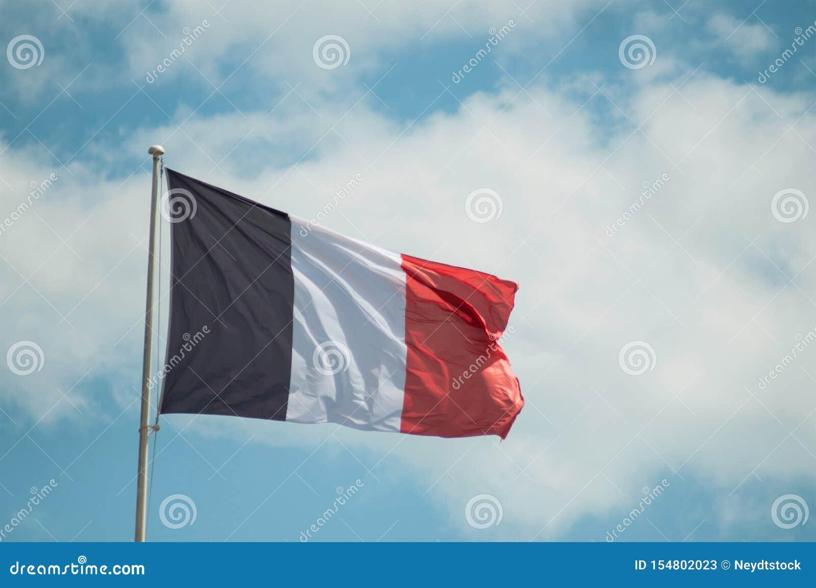 Drapeau français flottant sur le fond de ciel nuageux
