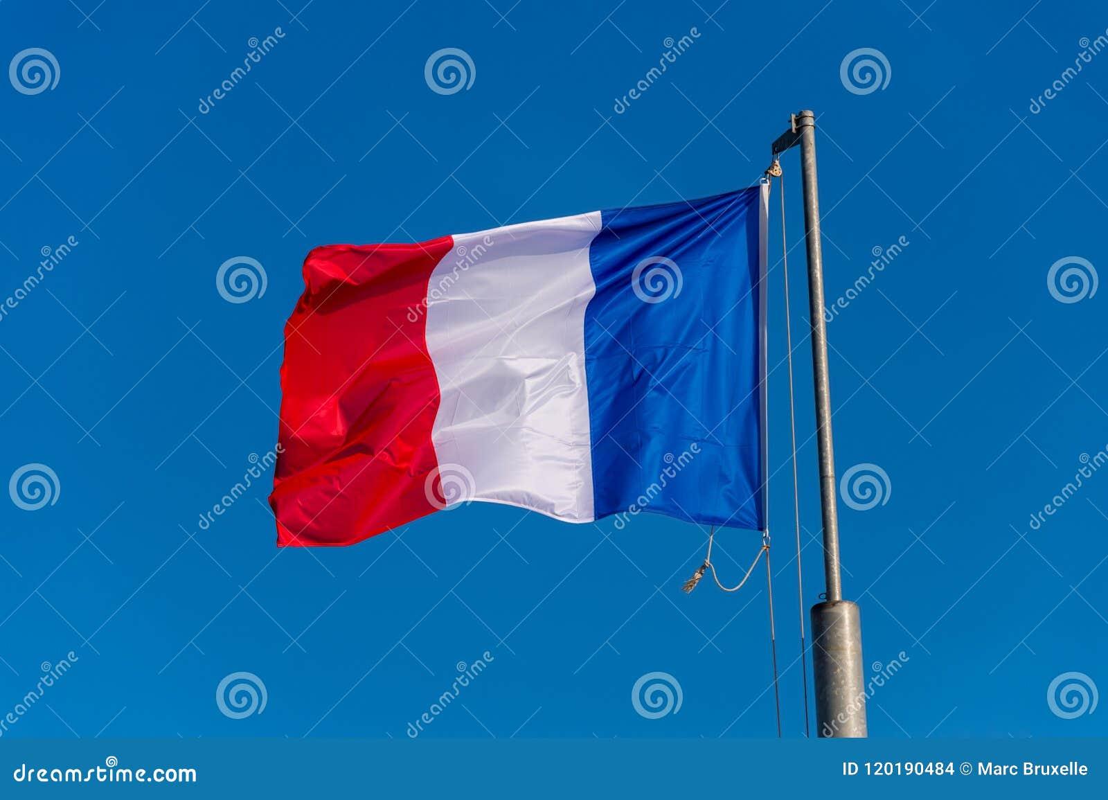 Drapeau français ondulant contre le ciel bleu
