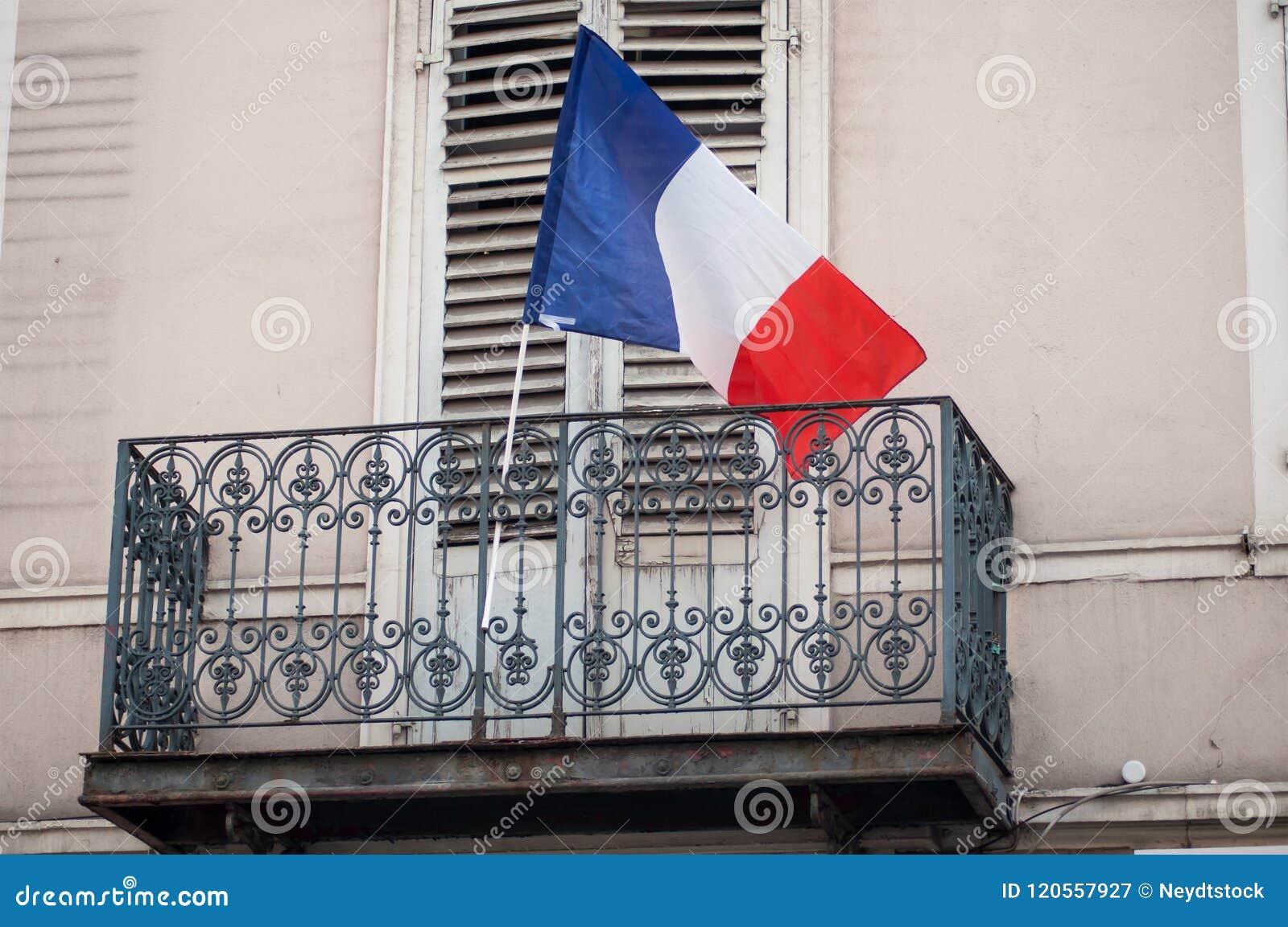Drapeau français sur le balcon de la façade de bâtiment