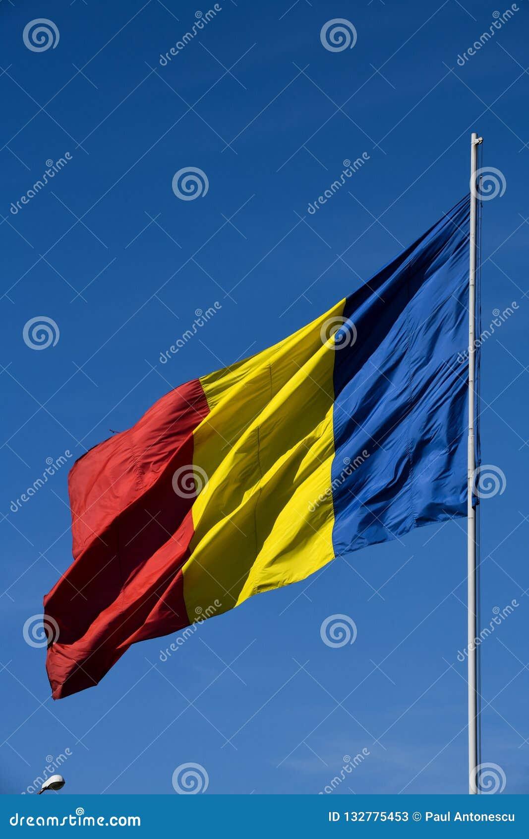 Drapeau roumain dans le vent un jour ensoleillé avec le ciel bleu clair