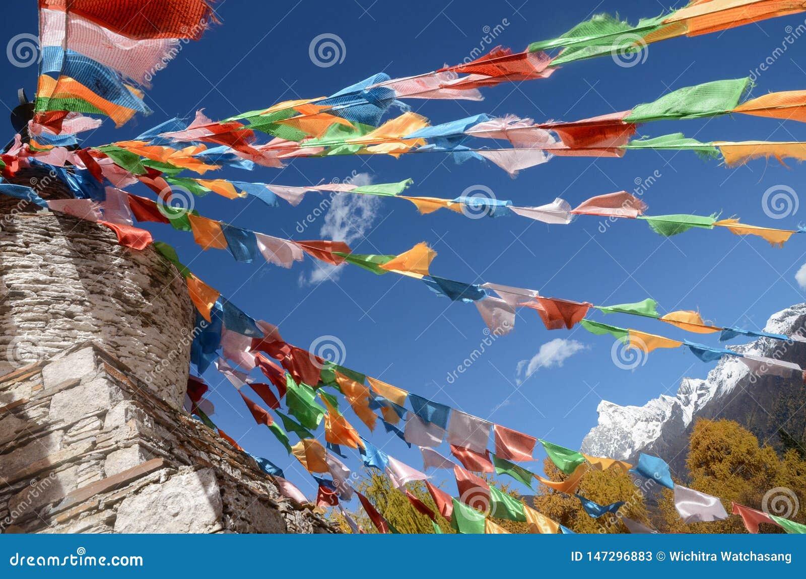 Drapeaux et montagne tib?tains color?s de neige ? la r?gion sc?nique de Siguniang, Chine