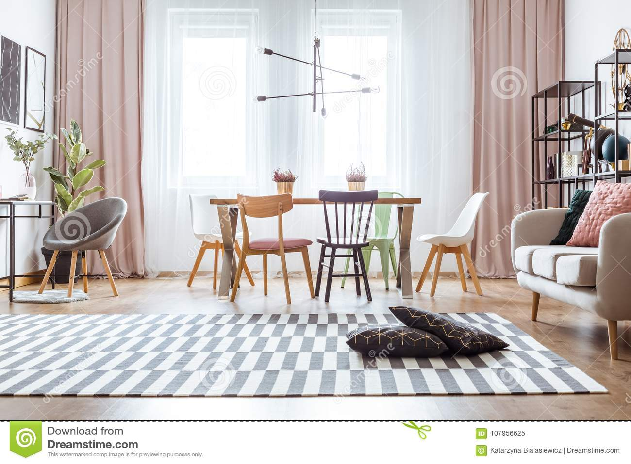 Black Pillows On Patterned Carpet And Pink Drapes In Cozy Living Room Interior With Chairs At Dining Table Near Sofa