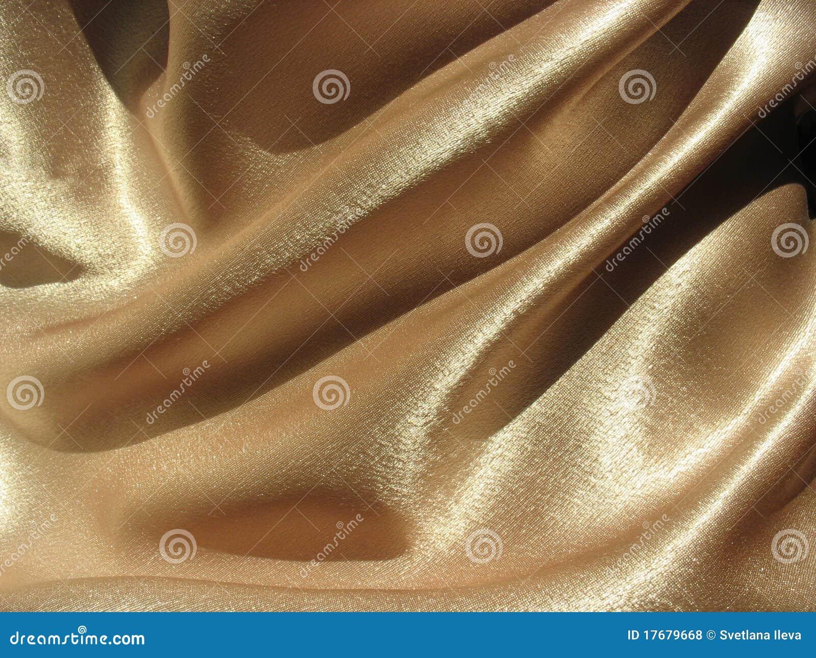 Drapujący złocisty atłasowy tło