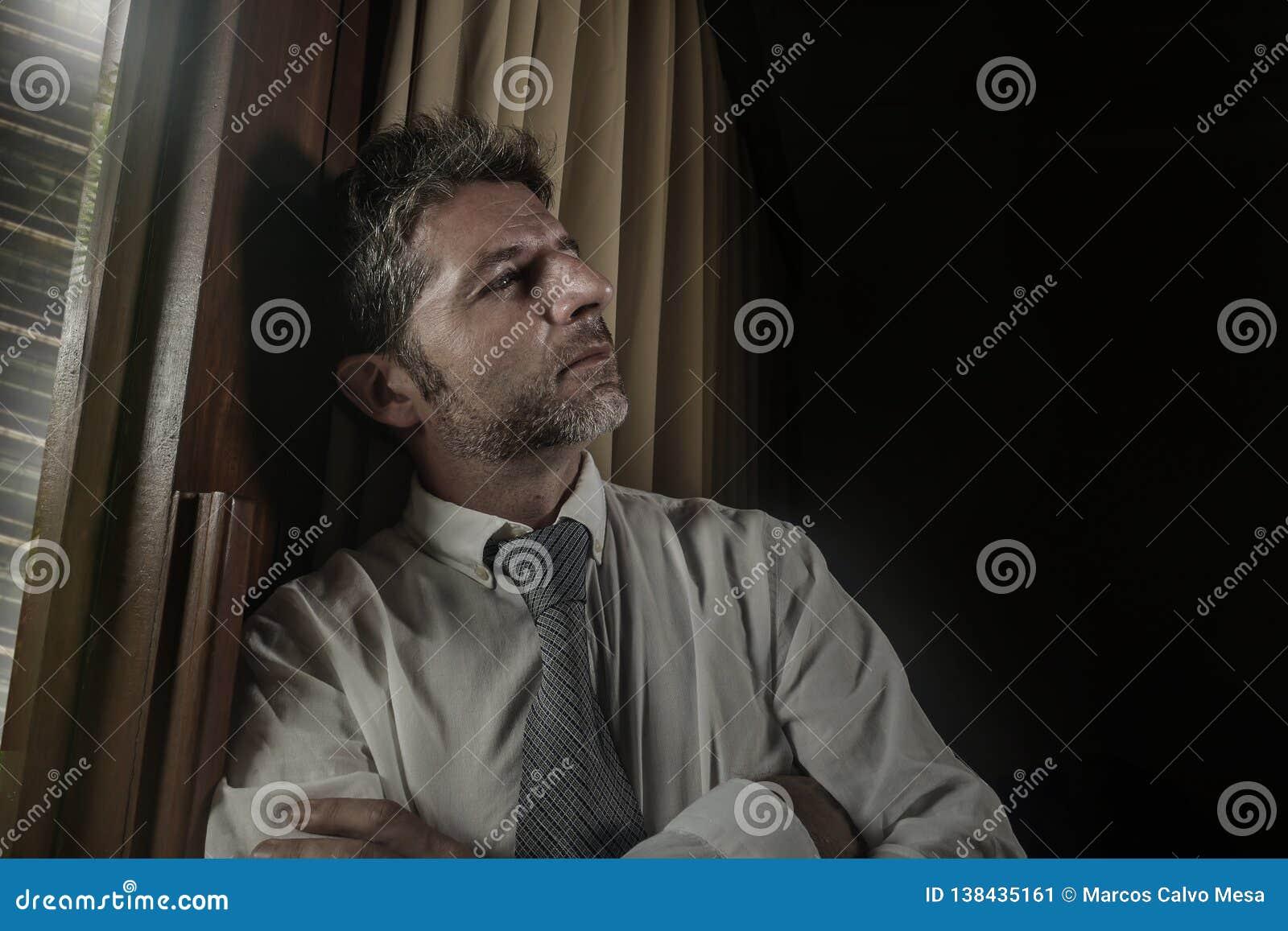 Drastisches Nachtlicht-Büroporträt des Geschäftsmannes gesorgt und frustriert auf dem Fenster spät sich lehnen bearbeitend durchd