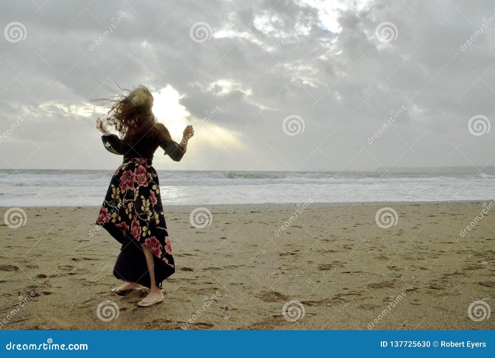 Drastisches Porträt langhaariger Dame in der Blumengesellschaftskleidung auf einem stürmischen Strand vor der Sonne