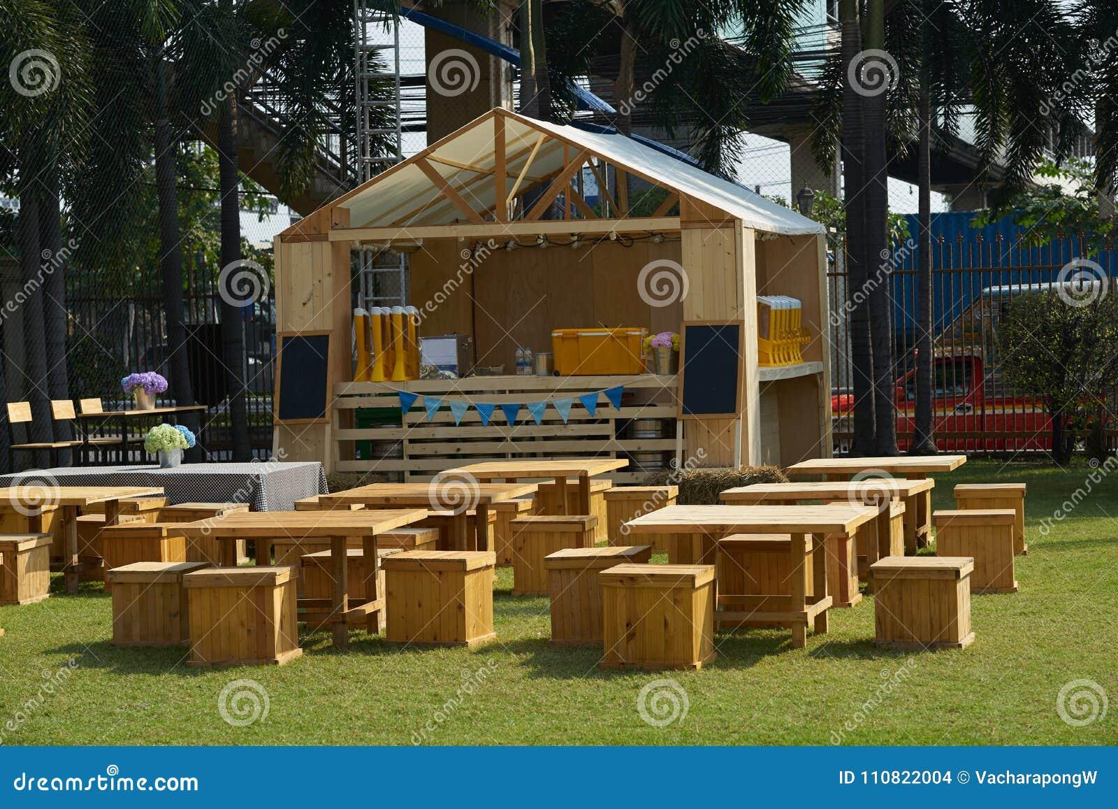 Draußen konfrontieren Restauranttabellen und Stühle und Zähler im Gras