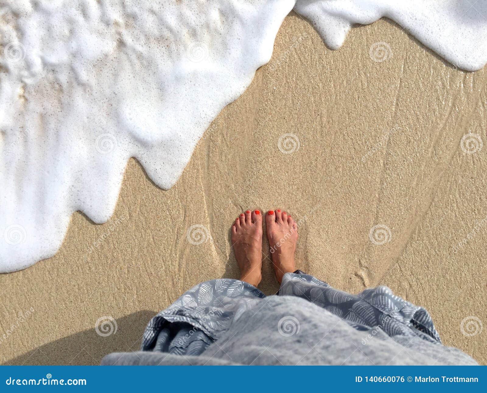 Draufsicht über weibliche Beine und Füße am Strand