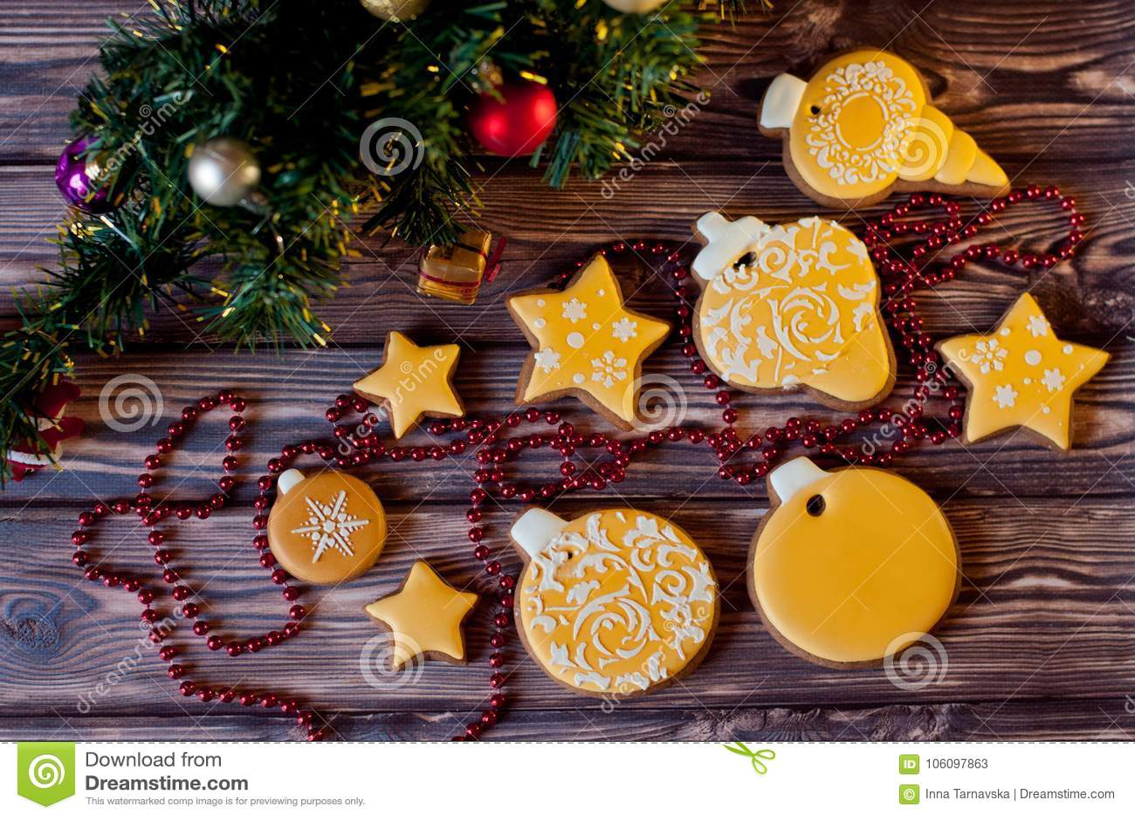 Draufsicht über Vielzahl des Gelbs glasierte ginferbread Plätzchen, die nahe Weihnachtsdekorationen auf hölzernen Hintergrund leg