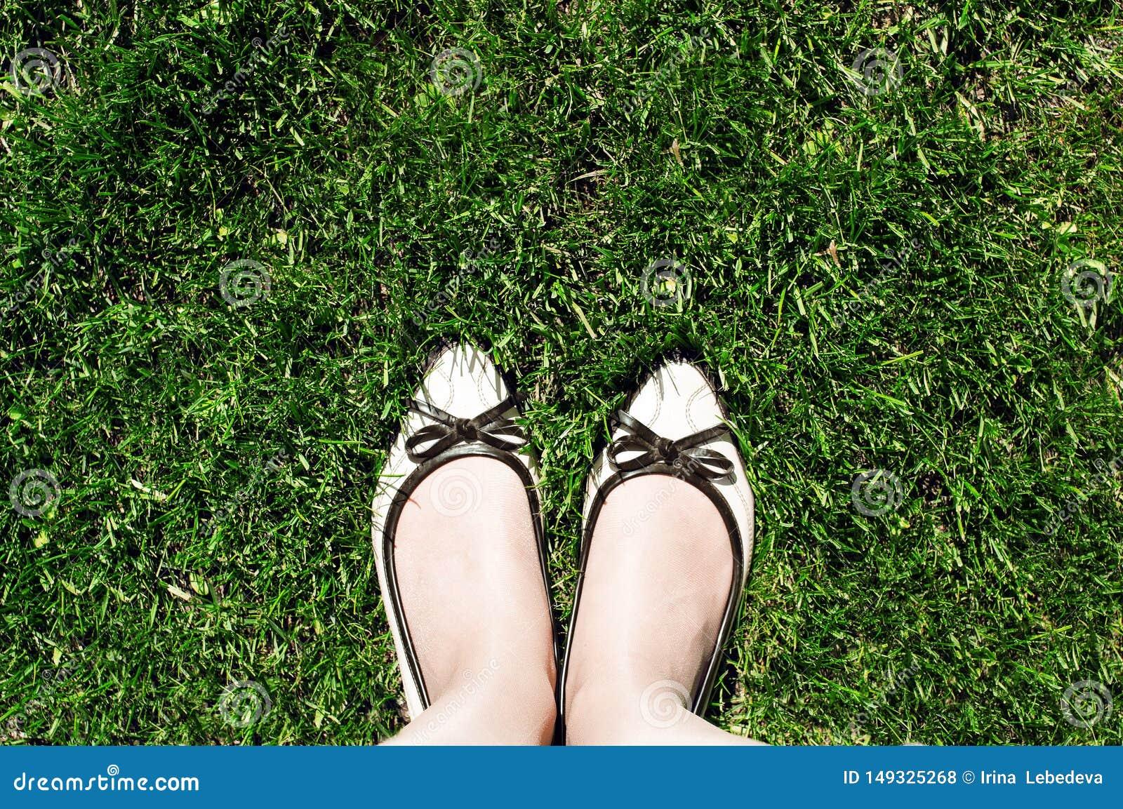 Draufsicht der beige Schuhe der Frauen, die auf dem gr?nen geschnittenen Gras stehen
