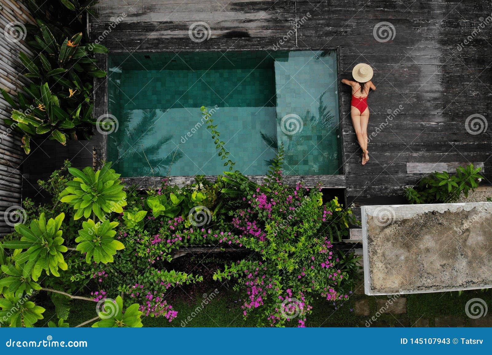Draufsicht der d?nnen Frau im Bikini und in Hut, die nahe Swimmingpool sich entspannen Raum f?r Text