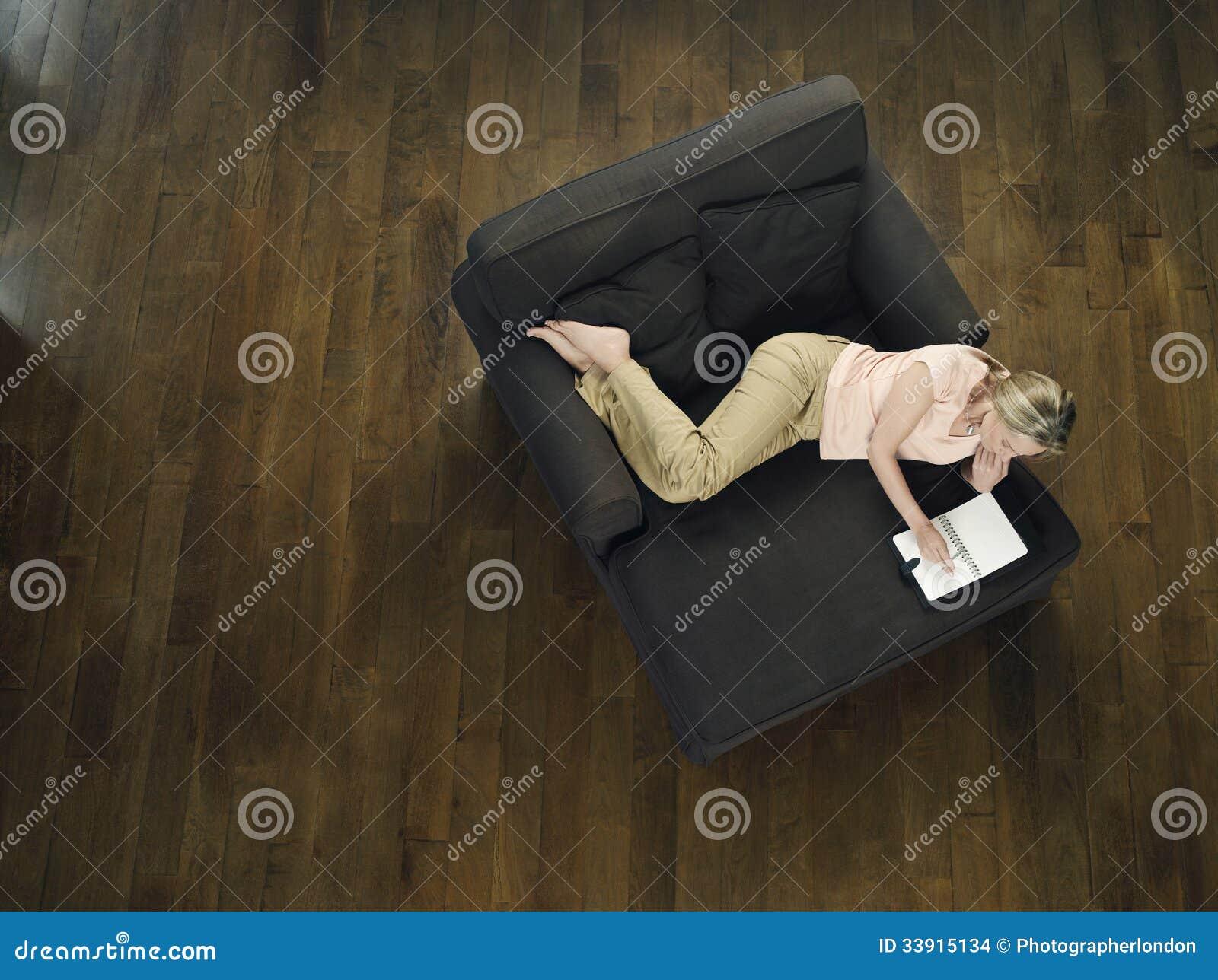 Draufsicht der Frau, die Laptop auf Sofa verwendet