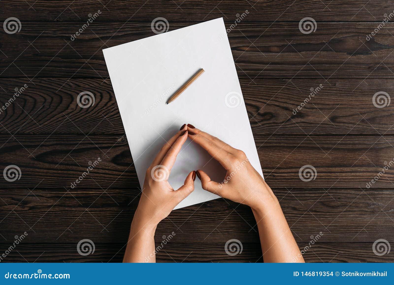 Draufsicht der H?nde der Frauen, bereit, etwas auf ein leeres Blatt Papier zu schreiben liegend auf einem Holztisch Wei?er Leerbe