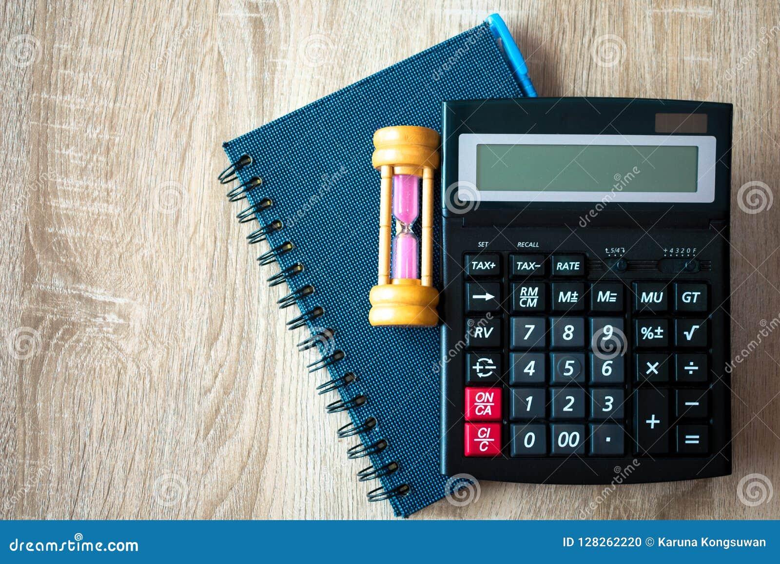 Draufsicht des hölzernen Arbeitsschreibtisches mit Anmerkungsbuch, Taschenrechner und hou