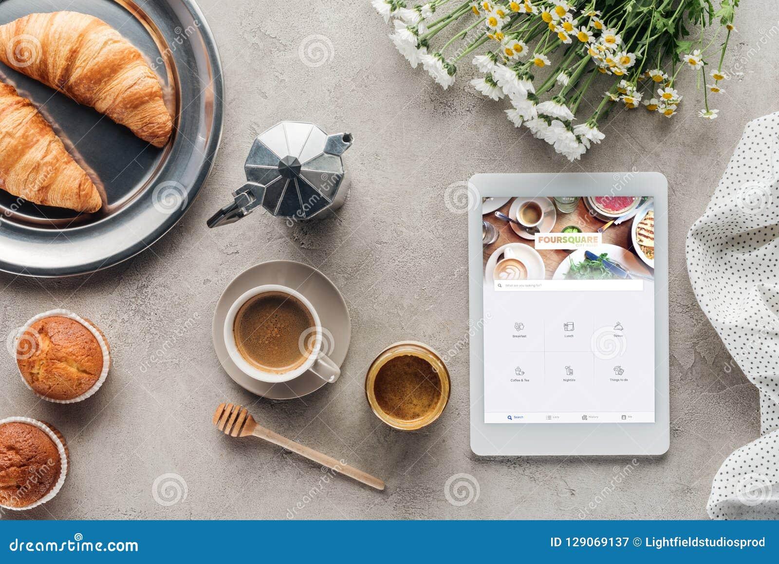 Draufsicht des Kaffees mit Gebäck und Tablette mit foursquare App auf Schirm