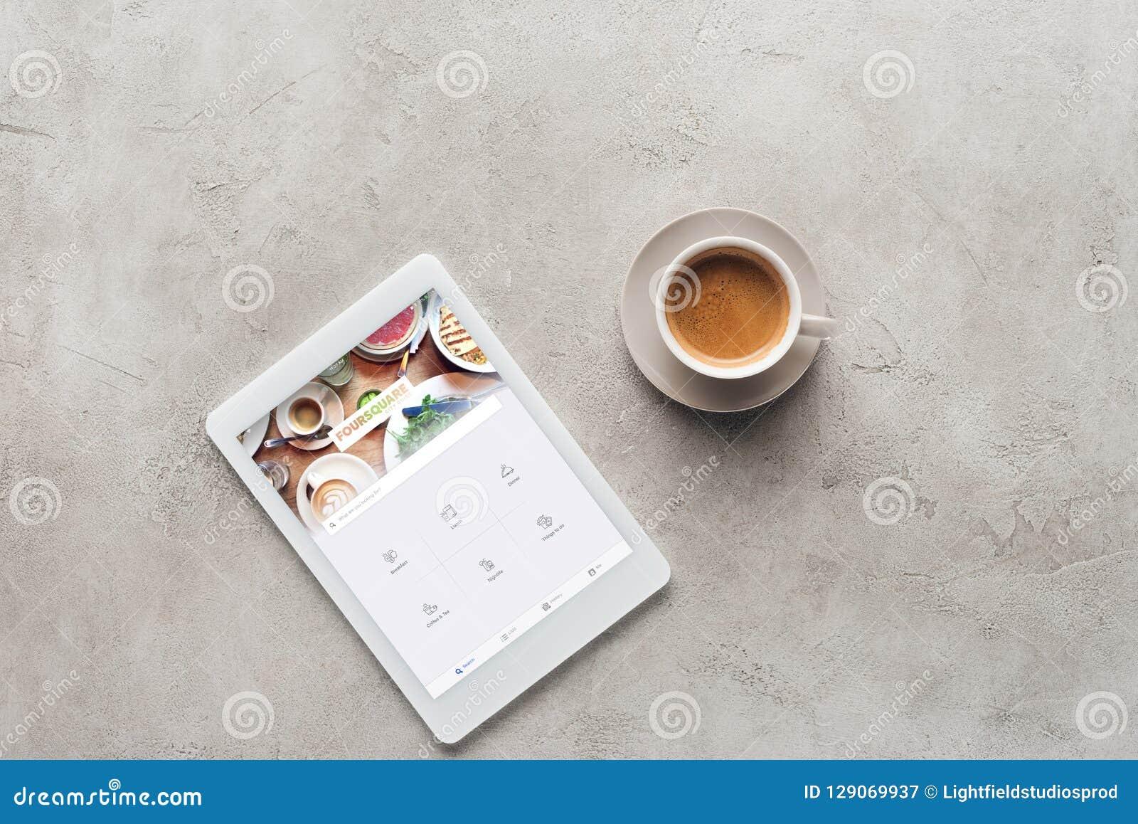 Draufsicht des Tasse Kaffees und der Tablette mit foursquare App auf Schirm