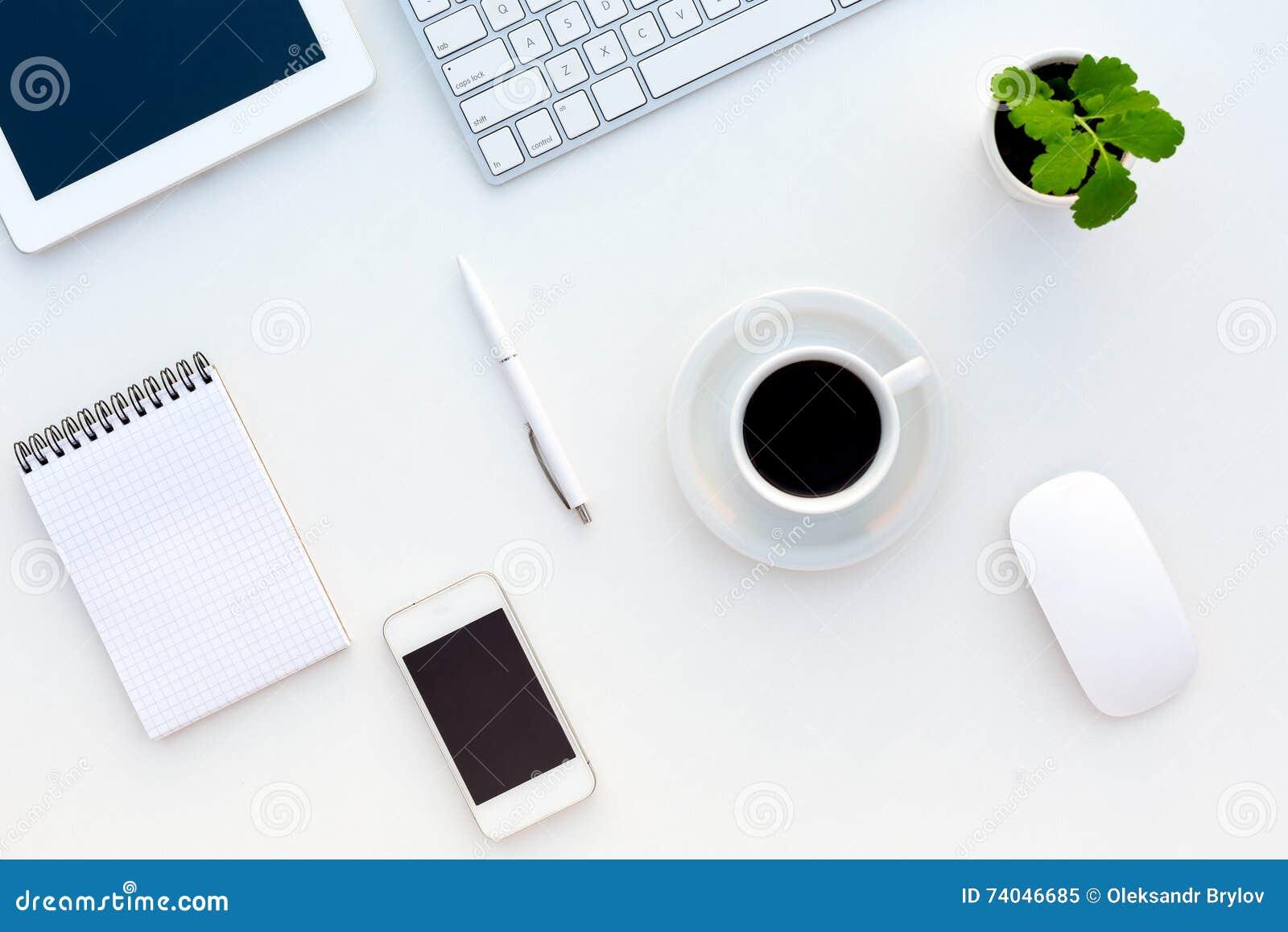 Draufsicht des weißen Schreibtischs mit modernem Elektronik-Briefpapier und Blume