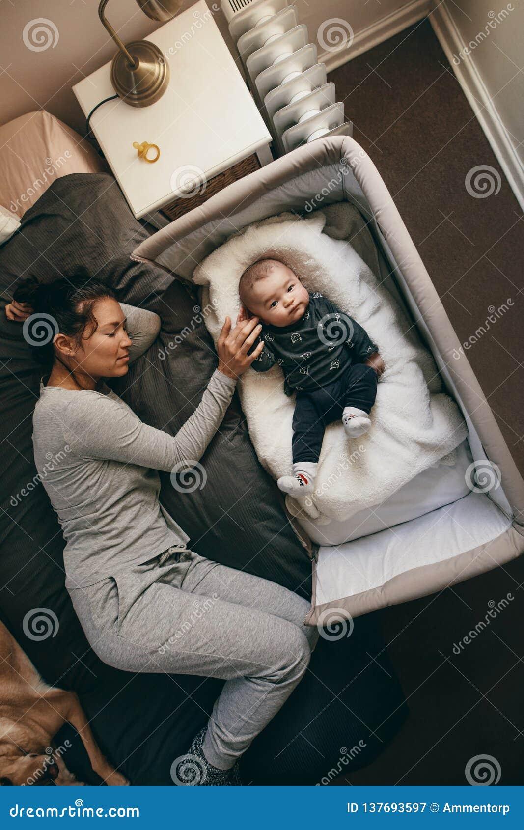 Draufsicht einer Mutter, die mit ihrem Baby schläft