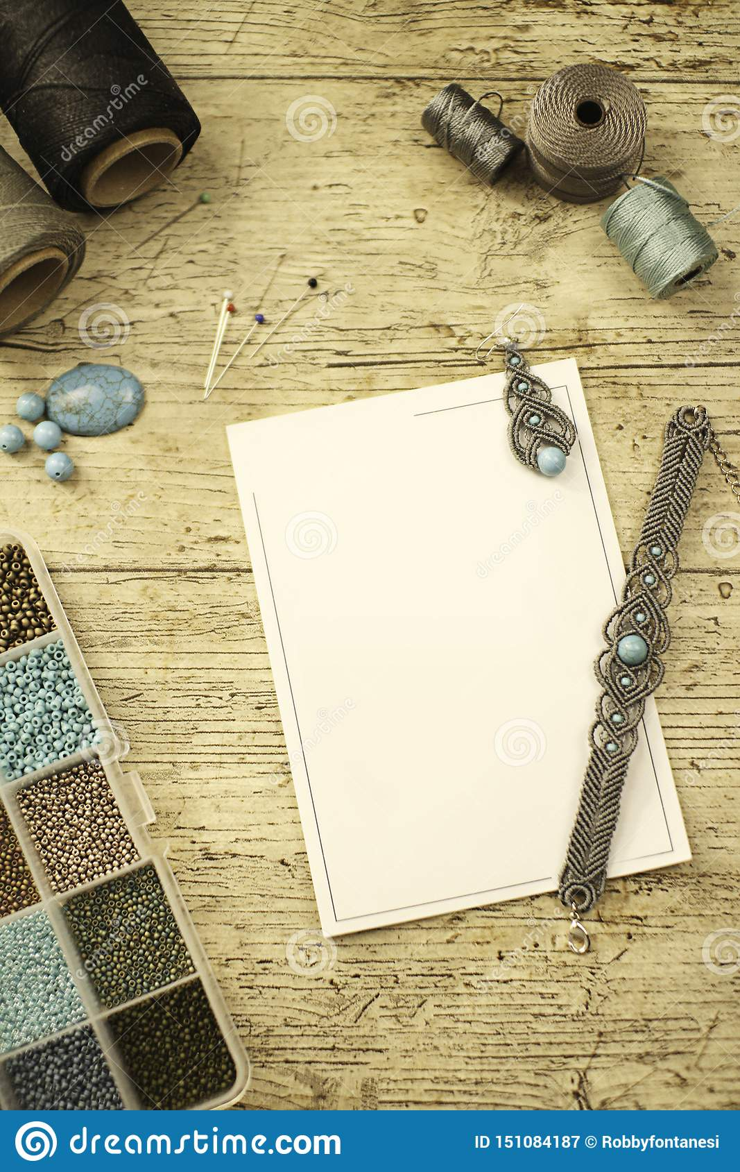 Draufsicht eines Holztischs mit Werkzeugen, Spulen des Fadens, den Natursteinen und farbigen Perlen, zum des Makrameeschmucks, mi