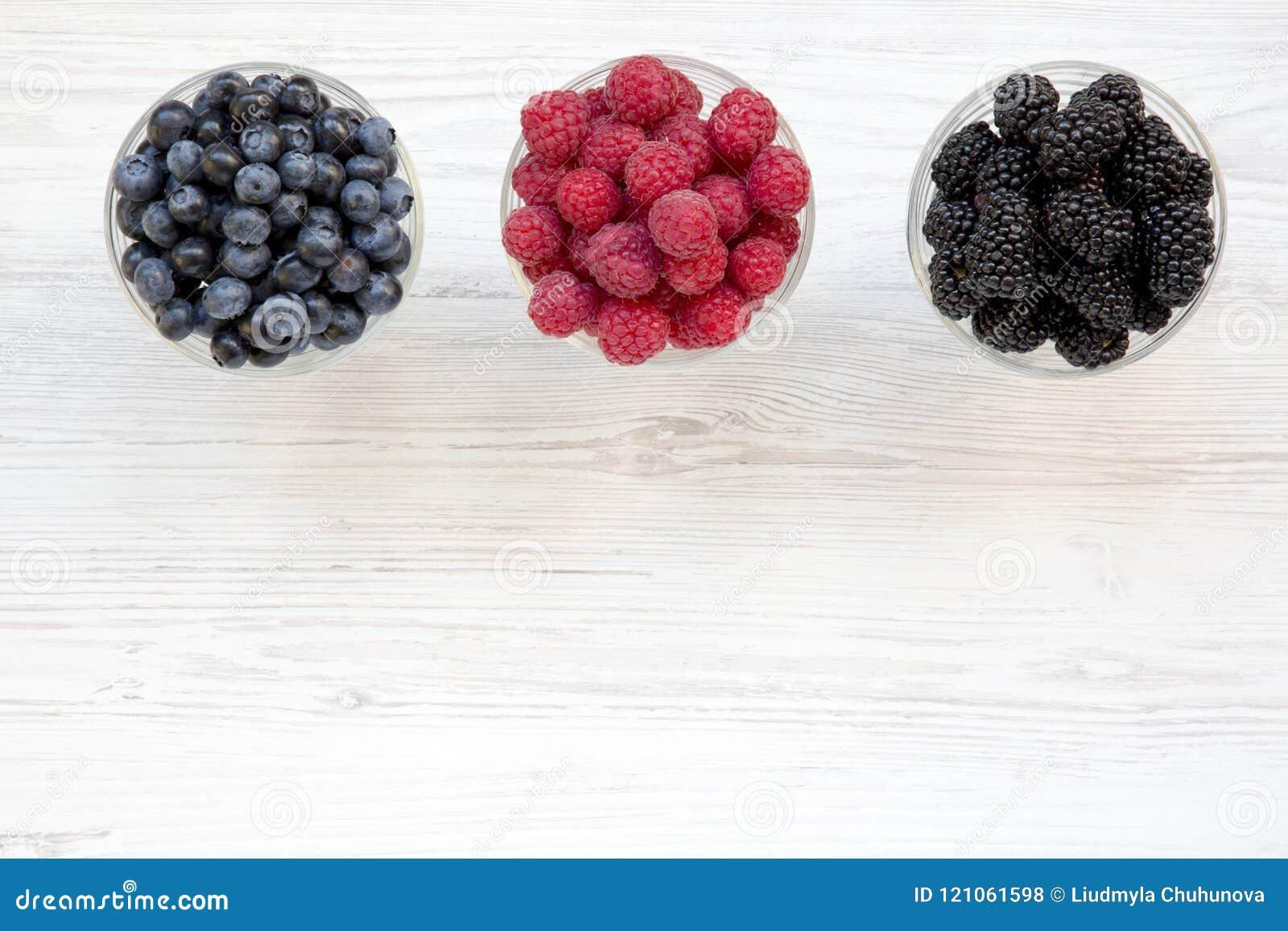 Draufsicht, Schüsseln, die Beeren enthalten: Blaubeeren, Brombeeren, Himbeeren Gesundes Essen und Nähren Von oben obenliegend