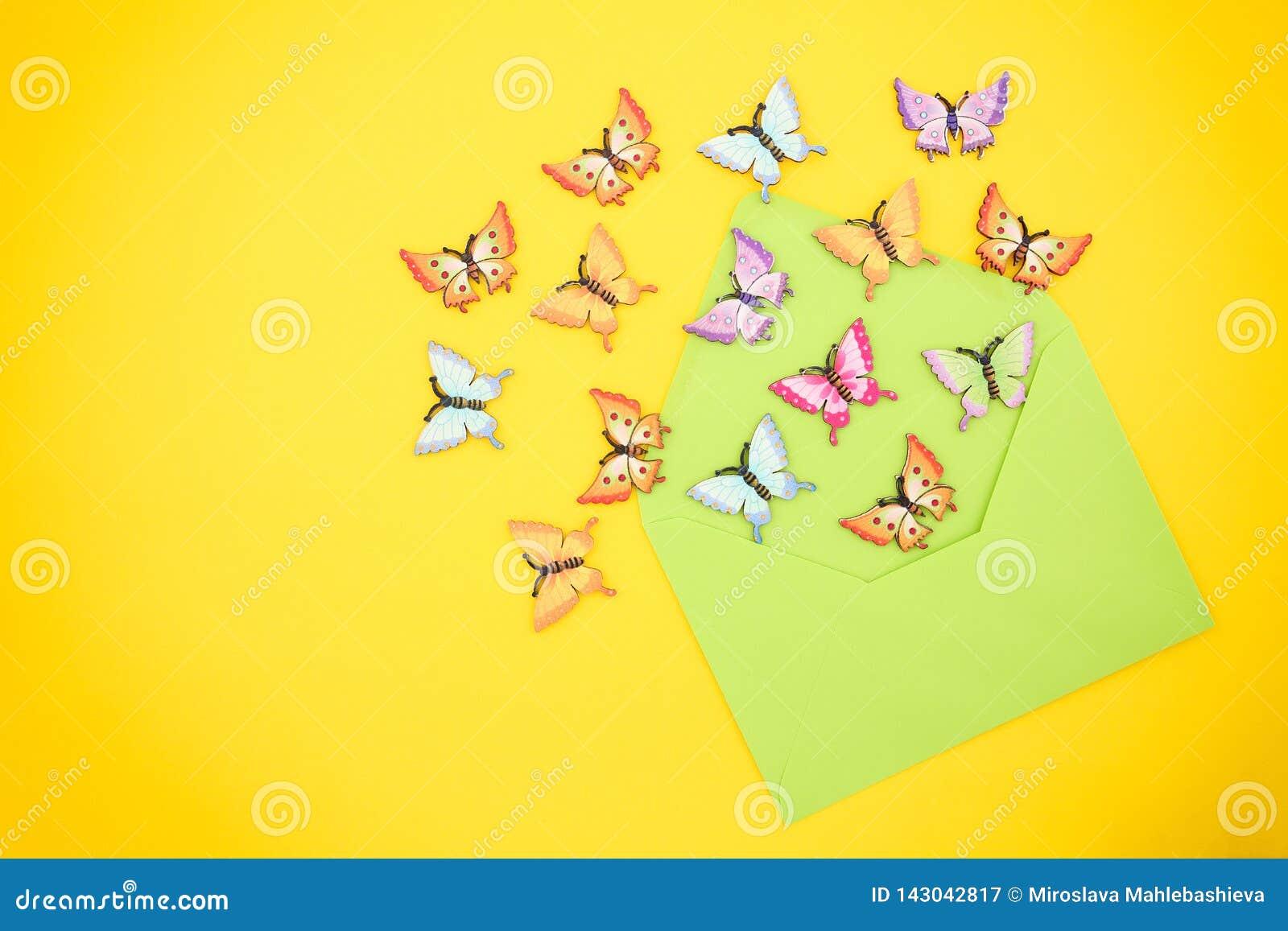 Draufsicht von den dekorativen, mehrfarbigen Schmetterlingen, die aus einen offenen, grünen Umschlag vom Recyclingpapier auf eine
