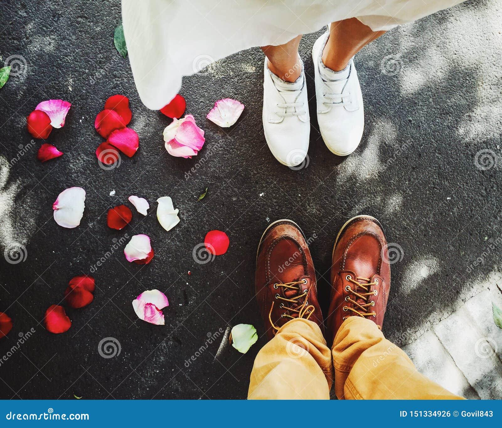 Draufsicht von Füßen eines jungen Paares mit wenigem schönem rotem rosafarbenem Blumenblatt aus den Grund