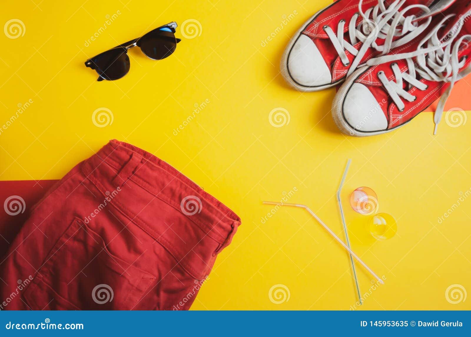 Draufsicht von roten Turnschuhen, von roten kurzen Hosen und von Sonnenbrille auf gelbem Hintergrund