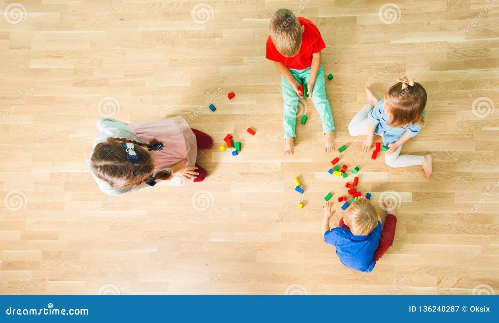 Draufsicht von vier Kindern, die aus Holzklötzen konstruieren