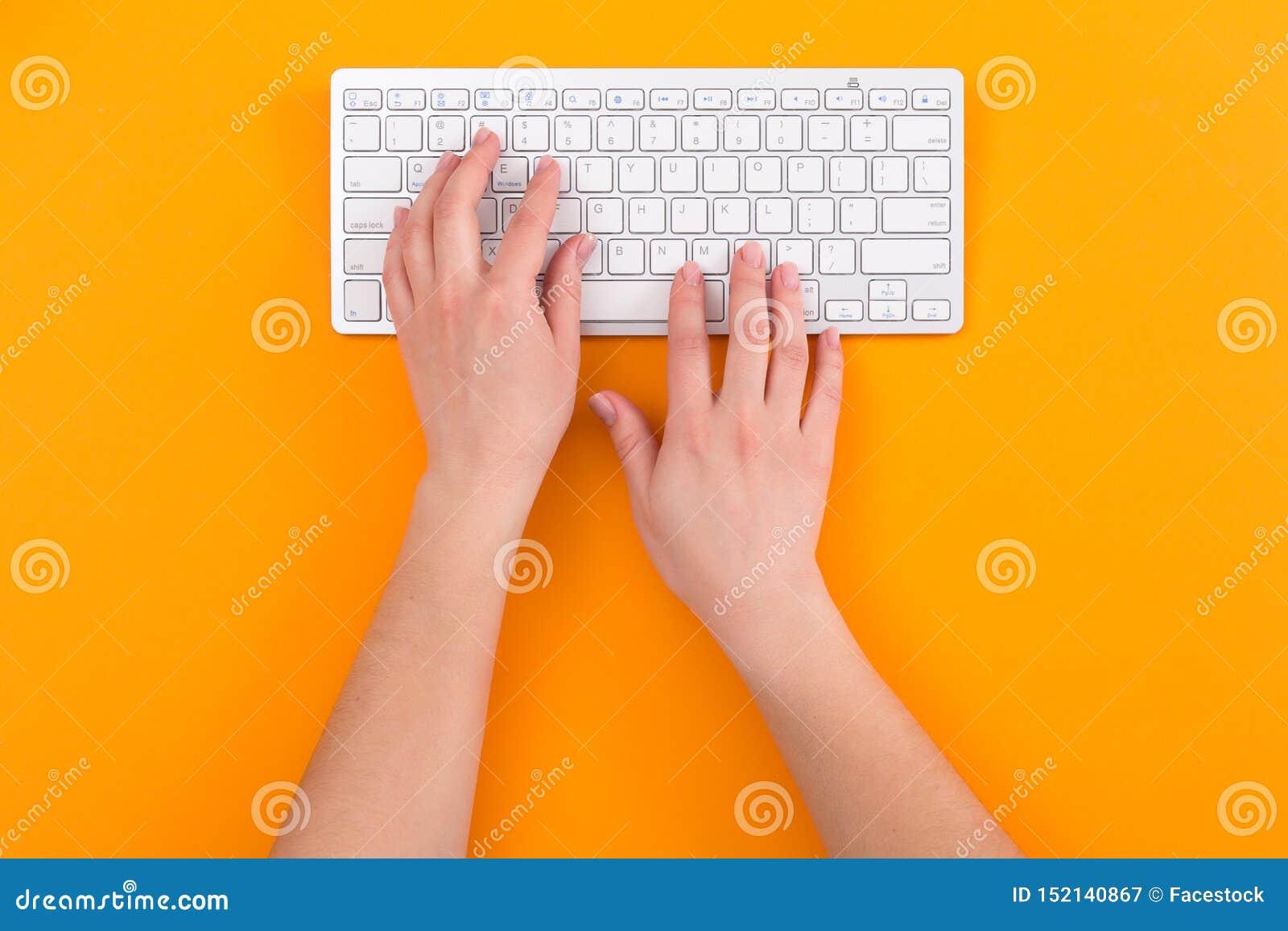 Draufsicht von weiblichen Händen unter Verwendung der Computertastatur beim Arbeiten, orange Hintergrund Die goldene Taste oder E