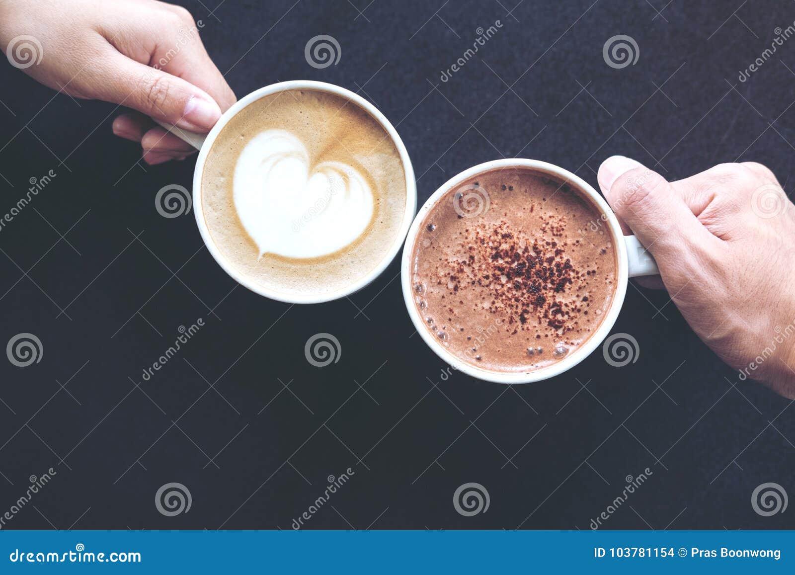 Draufsichtbild von Mann und Frau ` s übergibt das Halten von Schalen des Kaffees und der heißen Schokolade