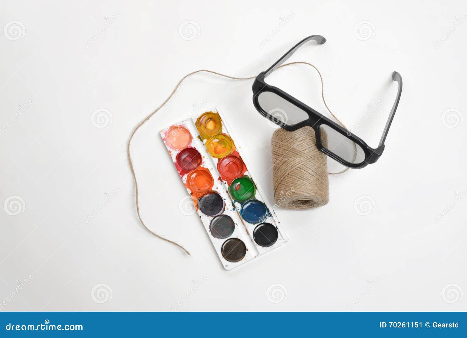 Draufsichtkunstszenenaufmachung der Threadschnur, der Gläser und der Aquarellfarben auf einem weißen Hintergrund