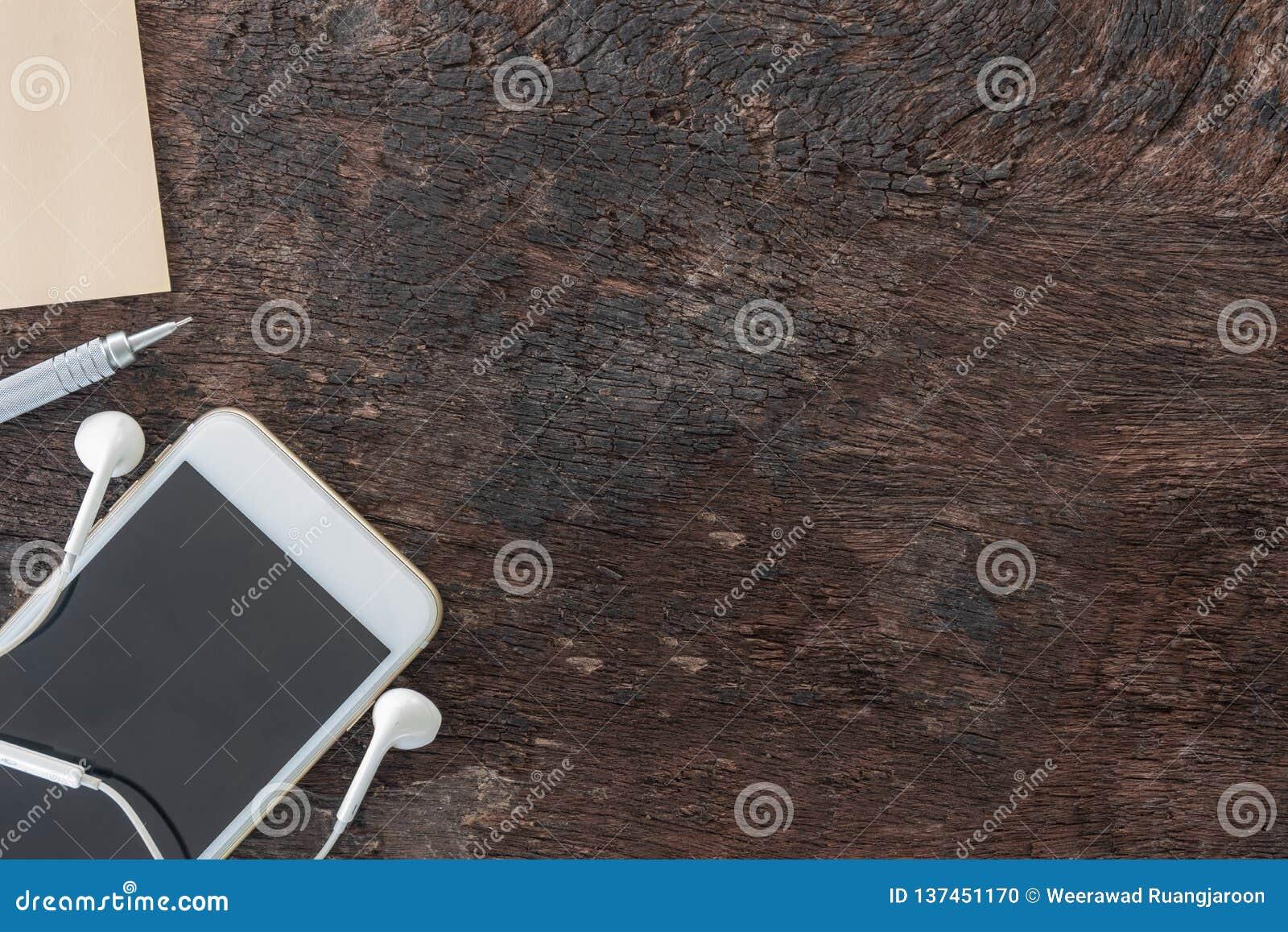 Draufsichtlaptop, Smartphone, Postenanmerkung, Bleistift und Kopfhörer auf altem hölzernem Hintergrund mit Kopienraum
