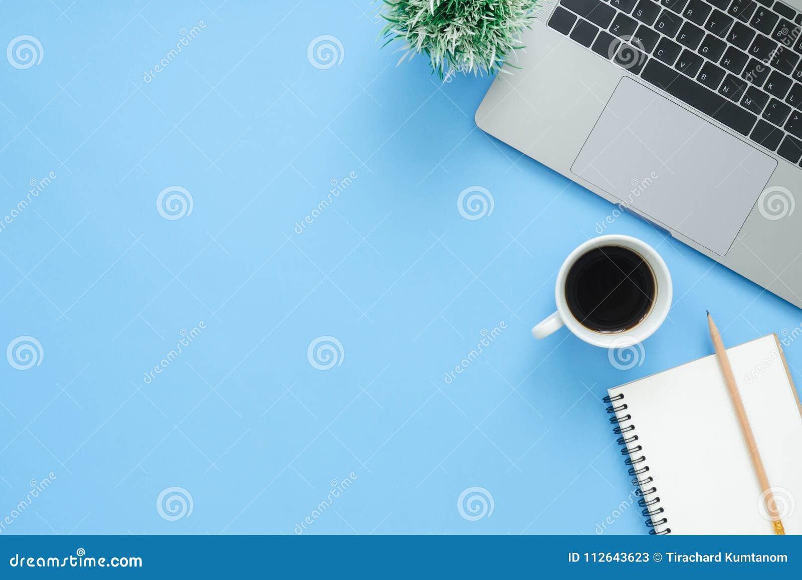 Draufsichtschreibtisch mit Laptop, Notizbüchern und Kaffeetasse auf blauem Farbhintergrund