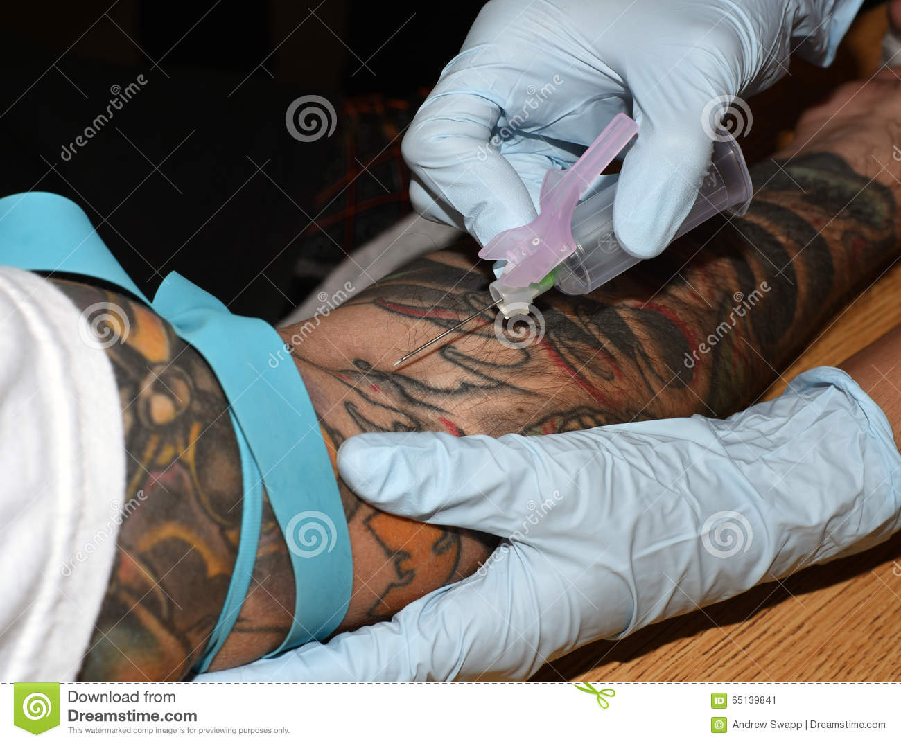 drawing blood from a tattooed arm stock photo
