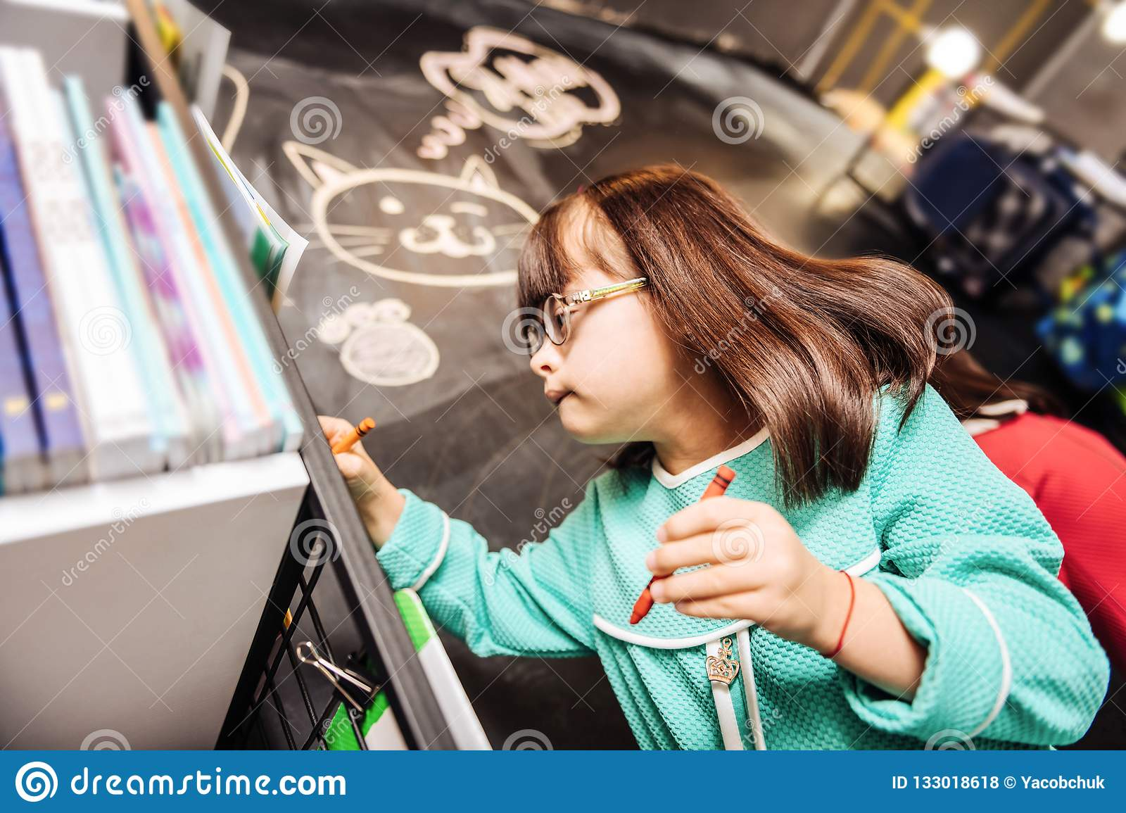 Cute pleasant girl with Down syndrome drawing cute cat on blackboard