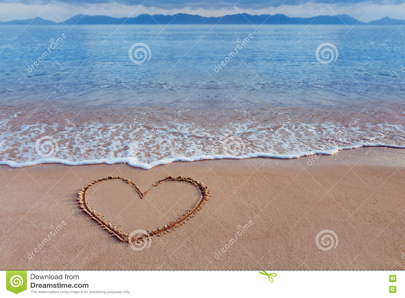 A drawing of a heart as a love symbol on a yellow sand at sea