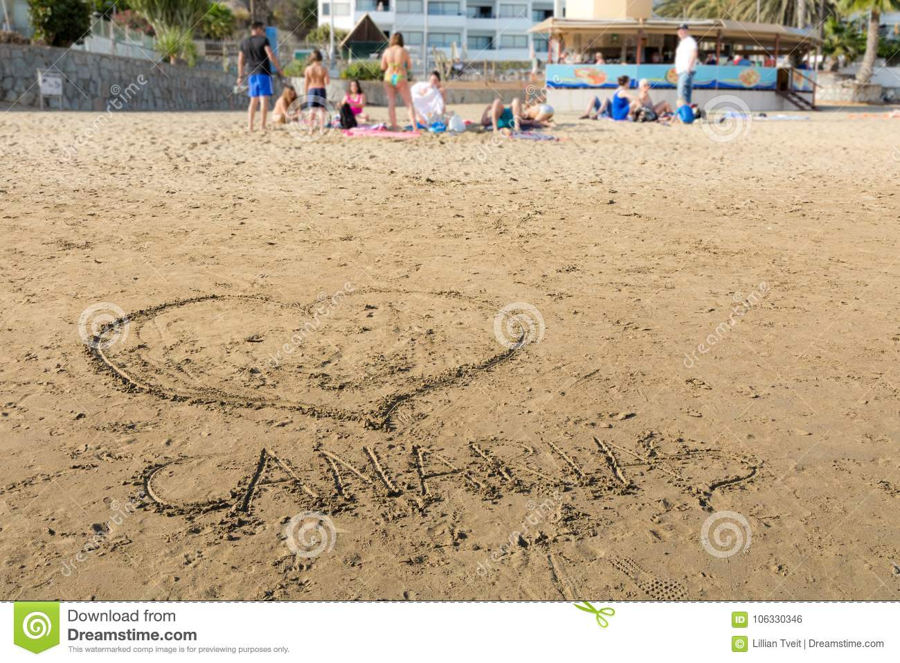 Drawings in the sand at Puerto Rico Beach in Gran Canaria, Spain. Soft background with people on the beach.