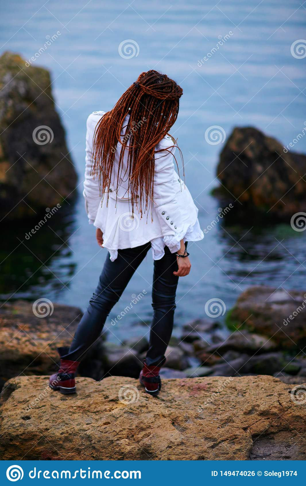Dreadlocks fashionable girl dressed in white jacket and black leather trousers posing near sea in the evening