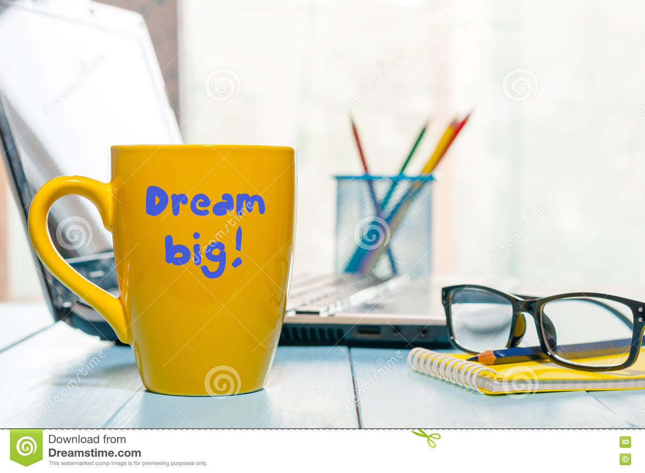 Dream big motivate and inspirational inscription on morning coffee cup at home or business office workplace background