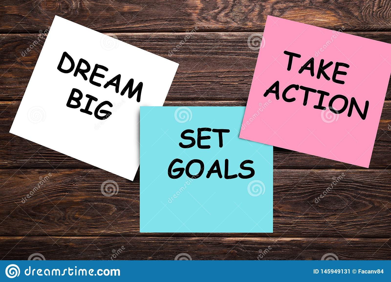 Dream big, set goals, take action concept - motivational advice or reminder on colorful sticky notes  on wooden table.