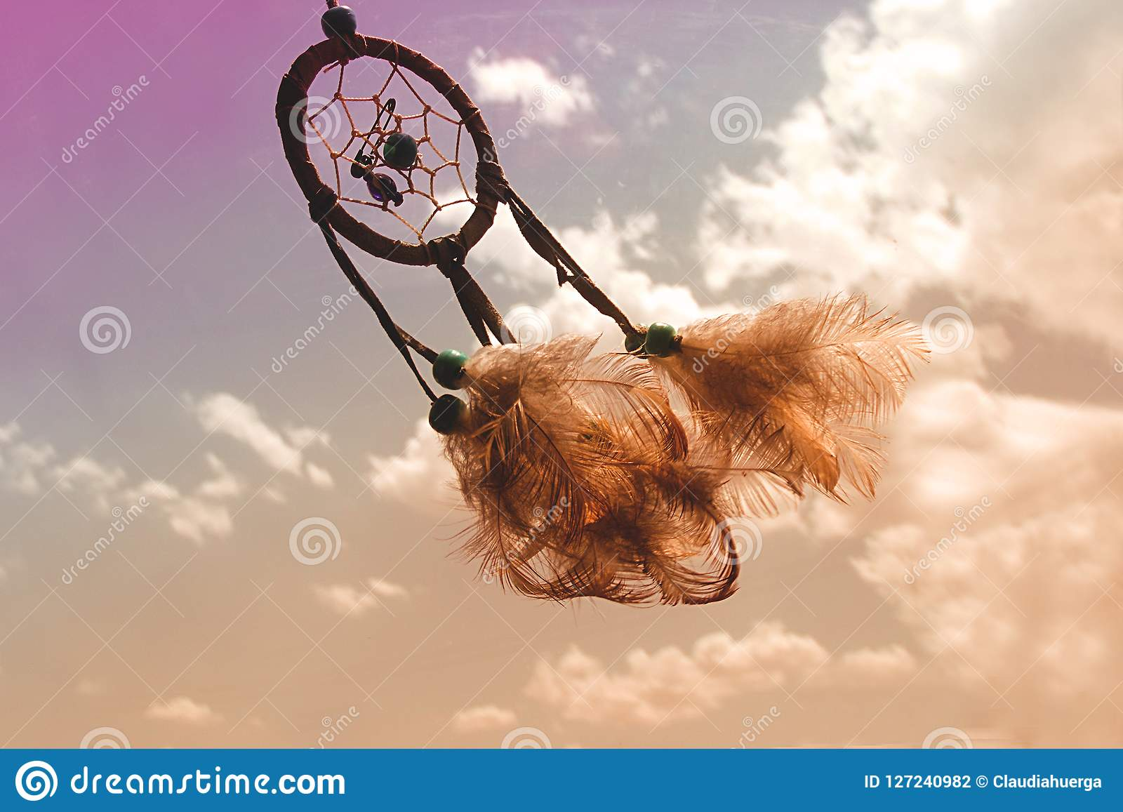 Dream catcher flying over a cloudy -colourful sky.