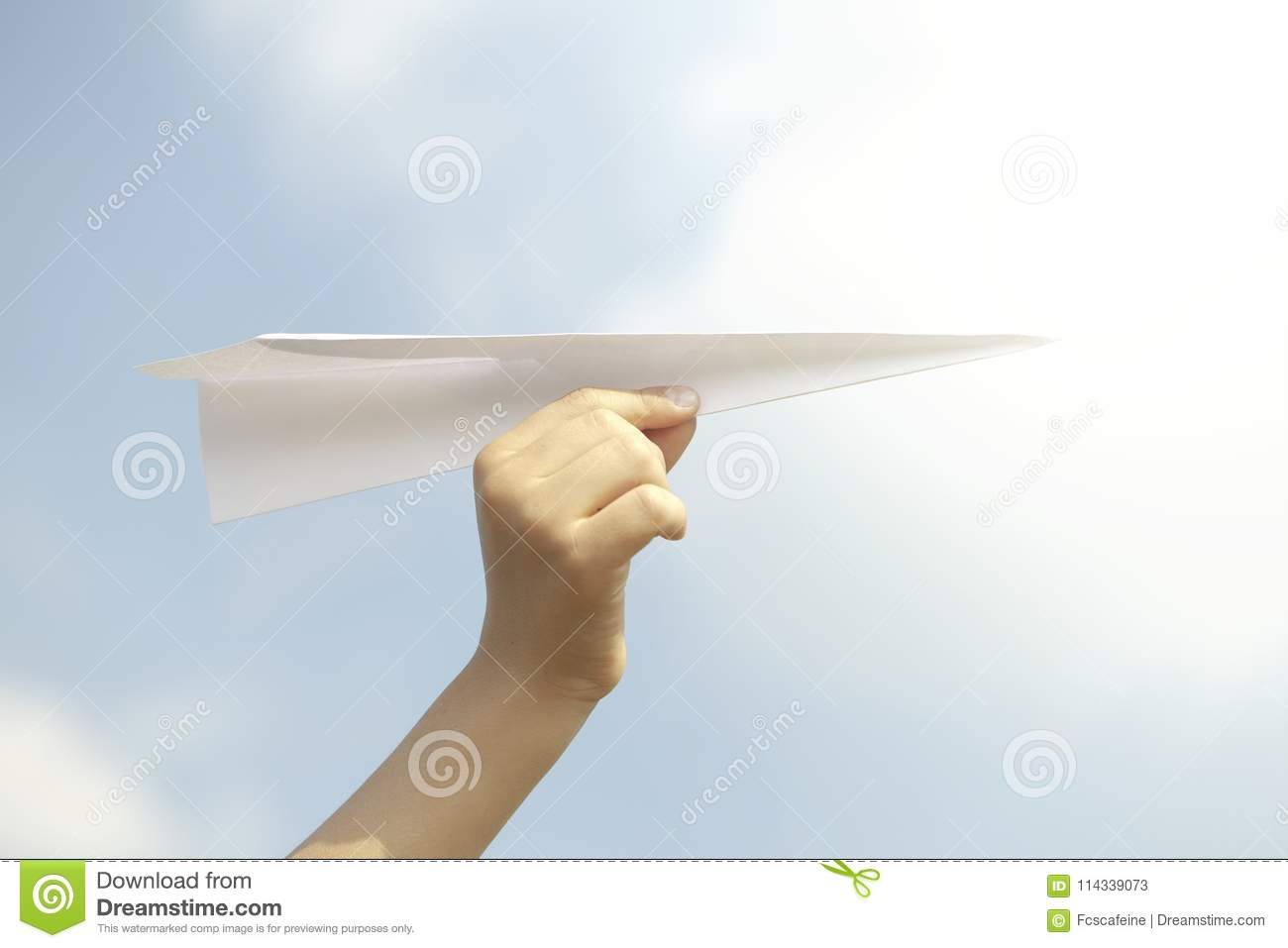Dream concept of a person flying a paper plane in the sky