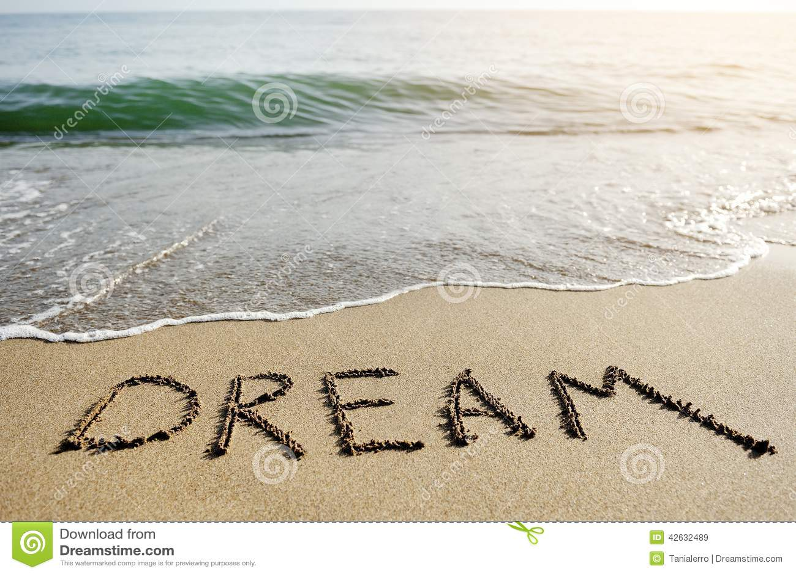 Dream word written on beach sand - positive thinking concept