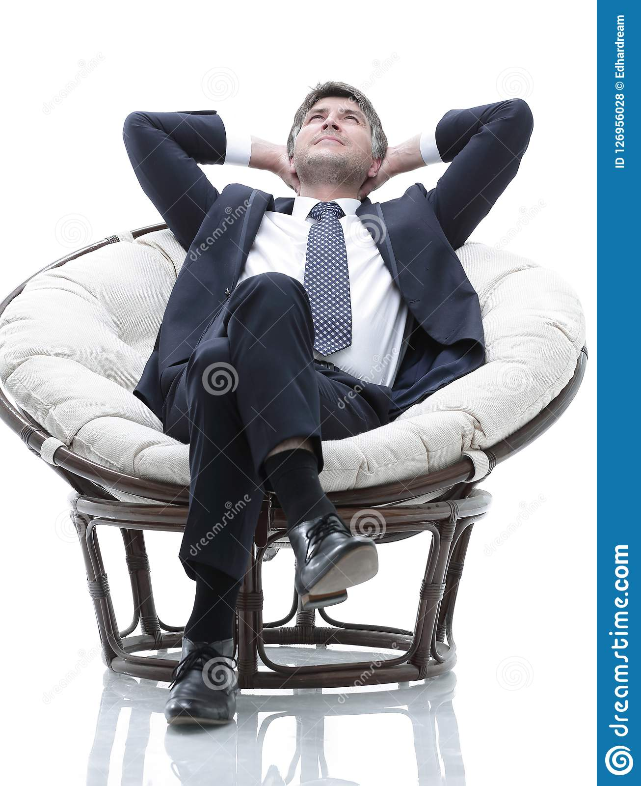 Dreaming businessman is resting, sitting in a large soft chair.